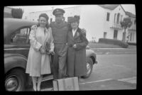 Ann Roth, P.F.C. Henry H. West, Jr. and Mertie West pose next to a car parked along North Ridgewood Place, Los Angeles, 1945
