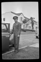 P.F.C. H. H. West, Jr. poses next to a car parked along North Ridgewood Place, Los Angeles, 1945
