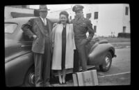 H. H. West, Ann Roth and P.F.C. Henry H. West, Jr. pose next to a car parked along North Ridgewood Place, Los Angeles, 1945