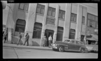 Mertie West stands outside the First National Bank of Fairbanks, Fairbanks, 1946