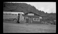 Mertie West walks past the bus at Paxson Lodge, Gulkana vicinity, 1946