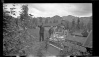 W. L. Kinsell, Mertie West and Frances Wells visit the spirit houses in Eklutna Historical Park, Eklutna, 1946