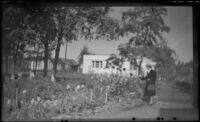 Mertie West stands by a flower garden, Anchorage, 1946