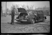 W. W. Witherby stands near the trunk of his car while stopping for lunch, Olancha, 1947
