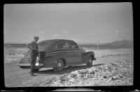 W. W. Witherby poses beside his car on the grade going to Panamint Valley, Death Valley National Park vicinity, 1947