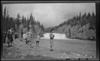 Mertie West stands on a riverbank in front of Bow Falls, Banff, 1947