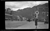 Mertie West stands on a sidewalk in downtown Banff, Banff, 1947
