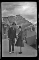 Mertie West and Assistant Manager Waterhouse stand at the bus station, Banff, 1947