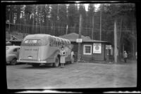 Mertie West poses beside the touring bus at Johnston Canyon, Banff National Park, 1947