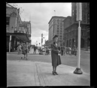 Mertie West stands on a street corner in front of the second Hotel Vancouver, Vancouver, 1947