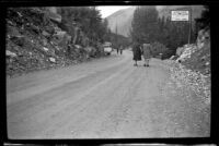 Mertie West and another woman stand on the road at Kicking Horse Tea Room, Field vicinity, 1947