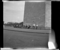 Mertie West seated at the base of the Washington Monument with other tourists, Washington, D.C., 1947