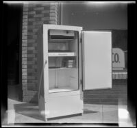 Woodlin electric refrigerator stands on a sidewalk with its door open, Los Angeles, 1948