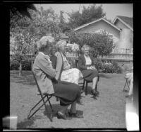 Mertie West, Josie Shaw and Hannah Lockwood sit around the McDonalds' backyard during a picnic, Burbank, 1948