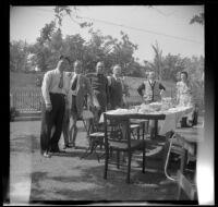 Everett Shaw, Hebard West, Lester Shaw, Will Shaw, J. W. McDonald and Chloe McDonald pose around a picnic table in the McDonalds' backyard, Burbank, 1948