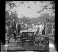 Members of the West, Shaw and McDonald families pose around a picnic table in the McDonalds' backyard, Burbank, 1948