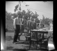 Everett Shaw, Hebard West, Lester Shaw, H. H. West, Will Shaw, J. W. McDonald and Chloe McDonald pose around a picnic table in the McDonalds' backyard, Burbank, 1948