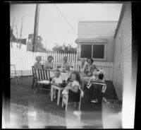 """Mertie West, Eva Newquist, Rudy Newquist, Anna Newquist, Maurine Bacon, Tommie Newquist and """"Punkie"""" Bacon pose while supping in the Bacons' backyard, Los Angeles, 1948"""