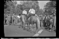 Shriners ride on horses as they enter Pershing Square during the 76th annual Shriners convention, Los Angeles, 1950