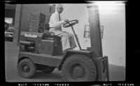 Glenn Harshbarger operates a Yardloader forklift outside the H. H. West Company's warehouse, Los Angeles, 1955