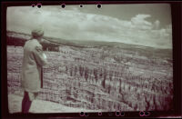 Mertie West gazing down into Bryce Canyon from a cliff edge, 1942