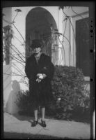 Mertie West wears a fur coat while posing outside her home, Los Angeles, 1947