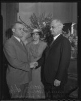 Ernest R. Utley is welcomed into the office of the Bankruptcy Court by Judge William P. James as wife Laura Utley watches, Los Angeles, 1936
