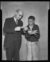 Ernest W. Fischer Jr. holds a carrier pigeon while Mayor P. H. McQuillen reads a letter, Upland, 1936
