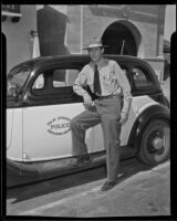 Police Chief C. W. Seaton leans on the new radio patrol car, Palm Springs, 1936