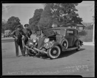 Officers W. A. Ellenson and J. S. Upwan examine a car wreck, Los Angeles, 1936