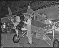 Louis Vremsak works on a plane with Del Hay, Los Angeles, 1936