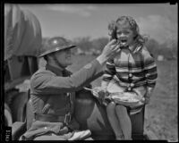 Private W.S. Pond gives food to Peggy Ann Duffy, Glendale, 1936