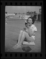 Second baseman Bernice Maxson applies make up on the field, Boston, 1936