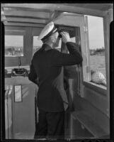 Captain Edward Hyde peers through his binoculars, Newport Beach, 1935
