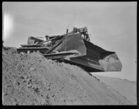 Unidentified worker sitting in a bulldozer, Calexico, 1936