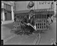 Inspector holds up metal rod meant to derail street car, Los Angeles, 1934