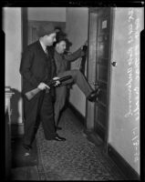 Captain Robert F. Underwood and Detective Lieutenant Richard B. McCreadie break down a door, Los Angeles, 1939