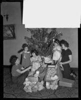 Sara Dudley, Annette Familian, Lillian Warde, Eleanor Schneider, Shirley Schneider and Dorothy Oviatt fill Christmas stockings, Los Angeles, 1934