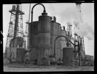 Storage tanks and derricks in an oil field, California, circa 1931