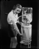 Photograph of a tennis player getting a glass of water from an Arrowhead water dispenser, Los Angeles, between 1935