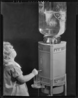 Photograph of Little girl getting a glass of water from a Puritas water dispenser, Los Angeles, between 1935