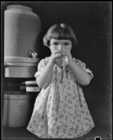 Photograph of a little girl drinking a glass of water, standing in front of a stoneware Arrowhead water cooler, Los Angeles, 1935