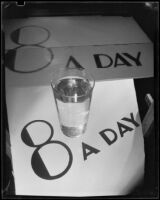 "Photograph with a glass of Arrowhead water on a sign reading ""8 A Day,"" Los Angeles, between 1935"
