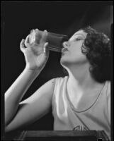 Photograph of a woman drinking a glass of Arrowhead Spring Water, Los Angeles, 1935