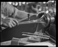 Technician applying a hammered finish to a trumpet bell at the F. E. Olds and Son plant, Los Angeles, 1933-1939
