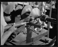 Technician making a brass horn at the F. E. Olds and Son plant, Los Angeles, 1933-1939