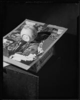 Still life type image of a stoneware cup resting on a photographic collage, resting on a cigar box