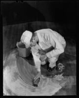 "Workman cleaning a floor with ""Double X Floor Cleaner,"" circa 1934"