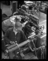 Two National Auto Shop technicians working at machinery, 1930-1950