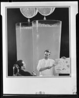 Photomontage image with a dentist showing a patient a chart with large glasses of orange juice behind them, 1935